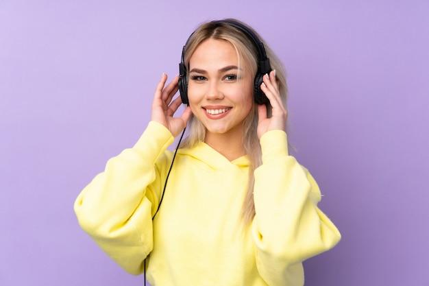 Chica adolescente sobre pared púrpura escuchando música