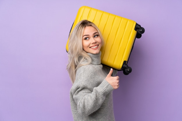 Chica adolescente sobre pared púrpura en vacaciones con maleta de viaje y con el pulgar hacia arriba