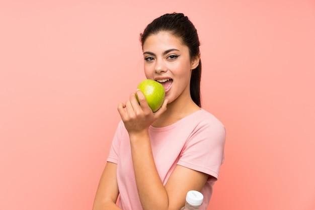 Chica adolescente sobre pared rosa aislada con una botella de agua y una manzana