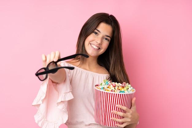 Chica adolescente sobre pared rosa aislada con gafas 3d y sosteniendo un gran cubo de palomitas de maíz