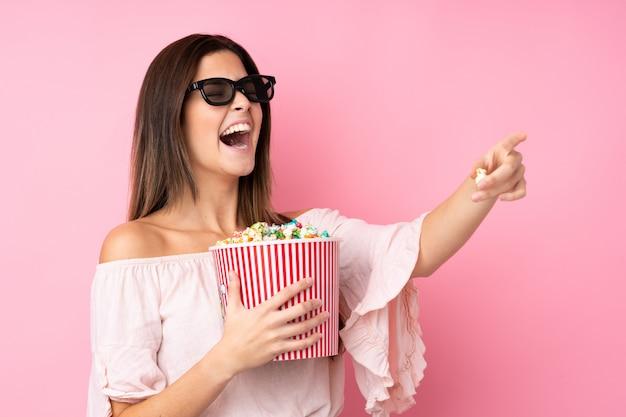 Chica adolescente sobre pared rosa aislada con gafas 3d y sosteniendo un gran cubo de palomitas mientras apunta lejos