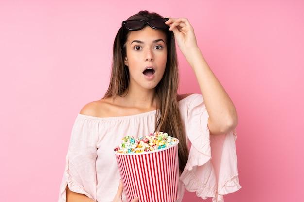 Chica adolescente sobre pared rosa aislado sorprendido con gafas 3d y sosteniendo un gran cubo de palomitas de maíz