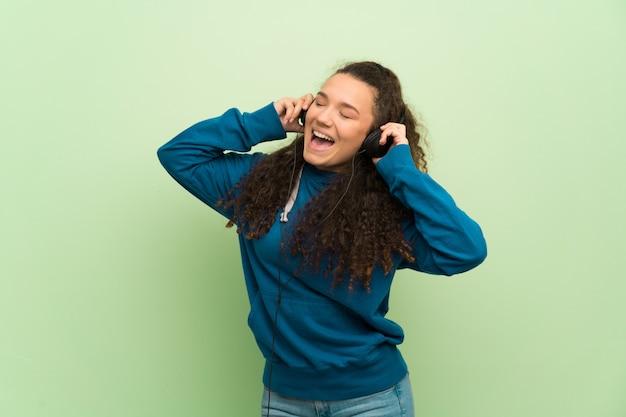 Chica adolescente sobre pared verde escuchando música con auriculares