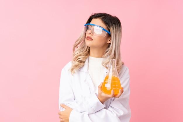 Chica adolescente sobre rosa aislado con un tubo de ensayo científico y mirando lateral