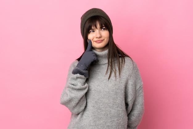 Chica adolescente con sombrero de invierno aislado en blanco pensando en una idea