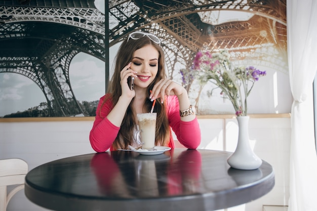 Chica adolescente sonriendo mientras habla por teléfono y con un batido de chocolate