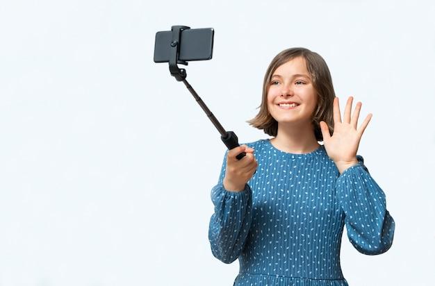 Chica adolescente sonriente mirando el teléfono inteligente y se comunicó con alguien
