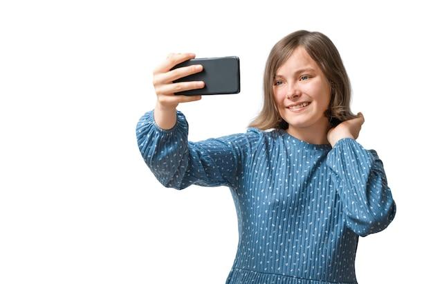 Chica adolescente sonriente mirando el teléfono inteligente