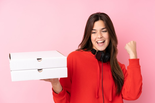 Chica adolescente sosteniendo cajas de pizzas sobre pared aislada