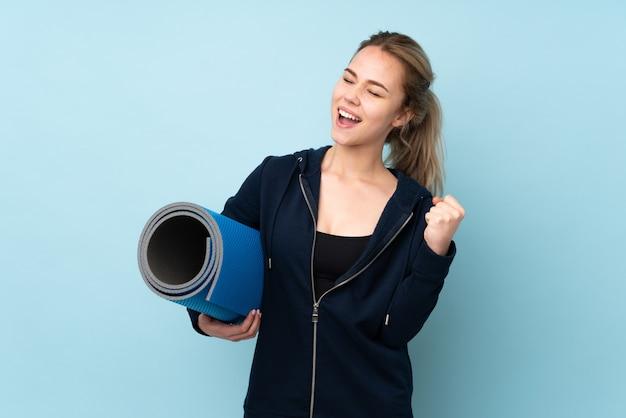 Chica adolescente sosteniendo estera en la pared azul celebrando una victoria