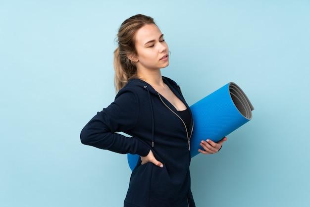 Chica adolescente sosteniendo estera en la pared azul que sufre de dolor de espalda por haber hecho un esfuerzo