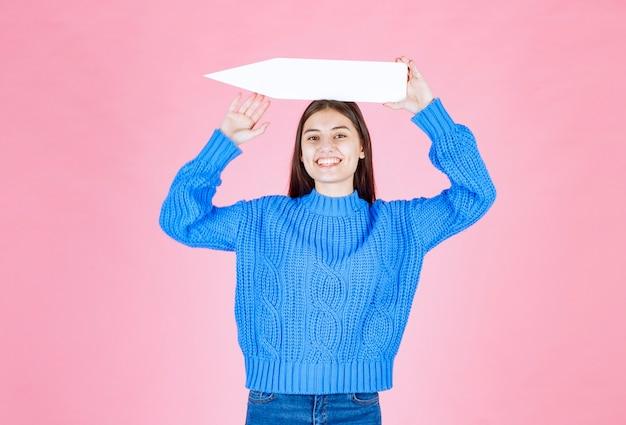 Chica adolescente sosteniendo una flecha de papel como un puntero a un lado.