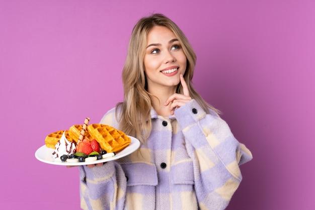 Chica adolescente sosteniendo gofres en la pared púrpura pensando una idea mientras mira hacia arriba