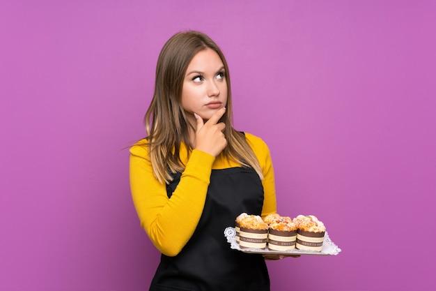 Chica adolescente sosteniendo un montón de mini tortas diferentes sobre fondo púrpura aislado pensando en una idea