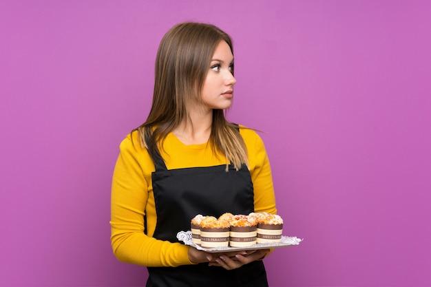 Chica adolescente sosteniendo un montón de mini tortas diferentes sobre el lado de aspecto púrpura aislado