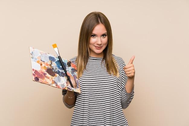 Chica adolescente sosteniendo una paleta sobre aislado dando un gesto de pulgares arriba