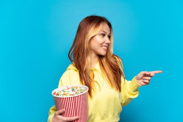 Chica adolescente sosteniendo palomitas de maíz sobre fondo azul aislado apuntando con el dedo hacia el lado y presentando un producto