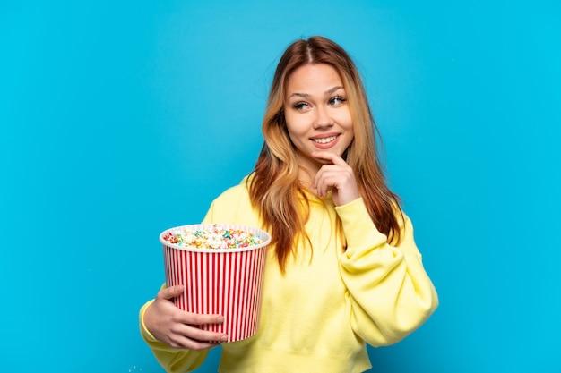 Chica adolescente sosteniendo palomitas de maíz sobre fondo azul aislado mirando hacia el lado y sonriendo