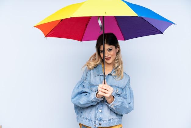 Chica adolescente sosteniendo un paraguas en la pared azul con expresión feliz