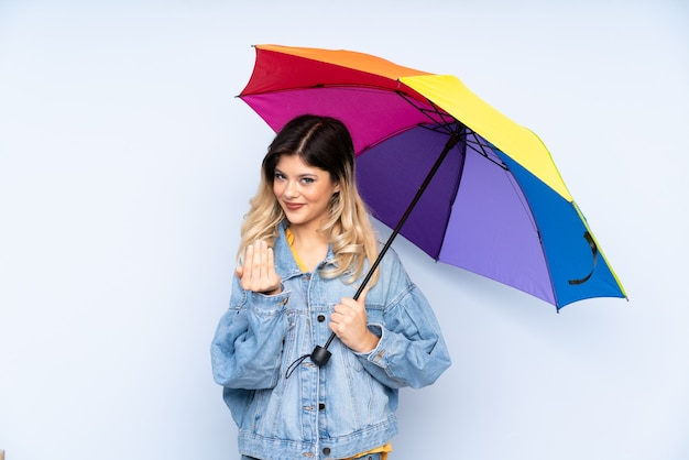 Chica adolescente sosteniendo un paraguas en la pared azul invitando a venir con la mano