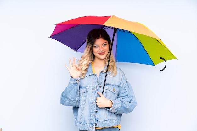 Chica adolescente sosteniendo un paraguas en la pared azul que muestra bien firmar con los dedos