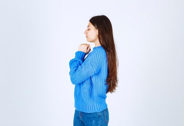 Chica adolescente en suéter azul pensando en algo en blanco.