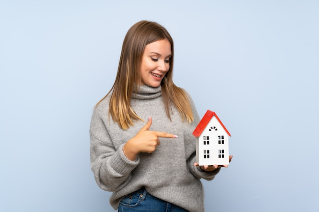 Chica adolescente con suéter sobre fondo azul aislado sosteniendo una casita