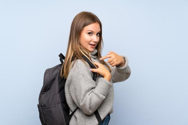 Chica adolescente con suéter sobre pared azul aislada con mochila