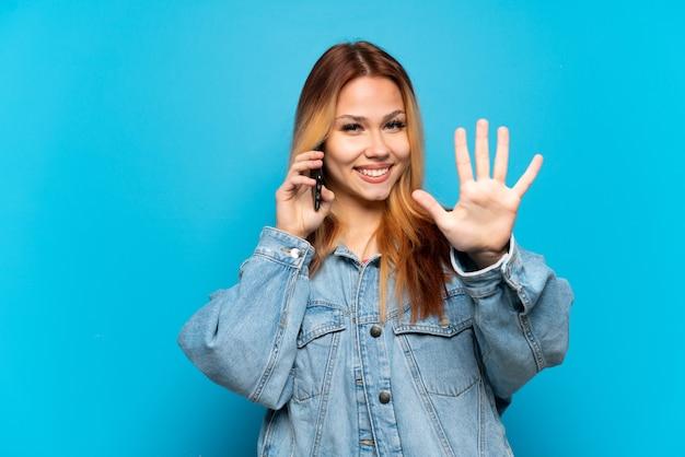 Chica adolescente mediante teléfono móvil sobre antecedentes aislados contando cinco con los dedos