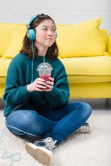Chica adolescente tomando zumo