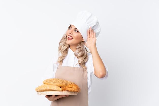 Chica adolescente en uniforme de chef. panadero de sexo femenino que sostiene una tabla con varios panes sobre blanco aislado que escucha algo