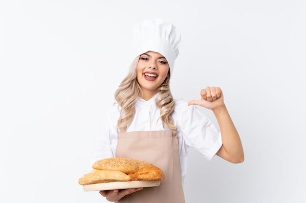 Chica adolescente en uniforme de chef. panadero de sexo femenino que sostiene una tabla con varios panes sobre fondo blanco aislado orgulloso y satisfecho de sí mismo