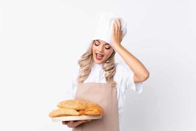 Chica adolescente en uniforme de chef. panadero de sexo femenino que sostiene una tabla con varios panes sobre fondo blanco aislado que tiene dudas con expresión de la cara confusa