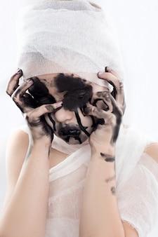 Chica adolescente con vendas de momia en halloween en blanco aislado