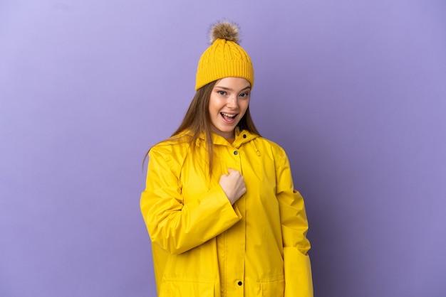 Chica adolescente vistiendo un abrigo impermeable sobre fondo púrpura aislado con expresión facial sorpresa