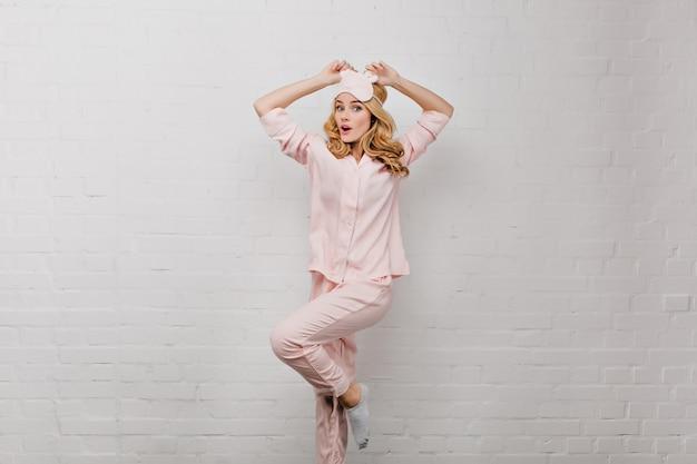 Chica adorable en calcetines grises bailando junto a la pared de ladrillos. señora bonita sorprendida en pijama de seda y antifaz que presenta en la pared blanca.