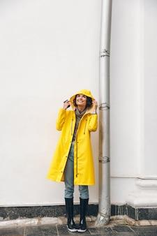 Chica adulta satisfecha 20s vistiendo abrigo amarillo de pie con capucha al mirar hacia arriba disfrutando de clima lluvioso con una sonrisa