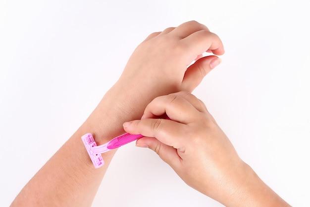 Chica afeita el pelo en su mano con navaja rosa