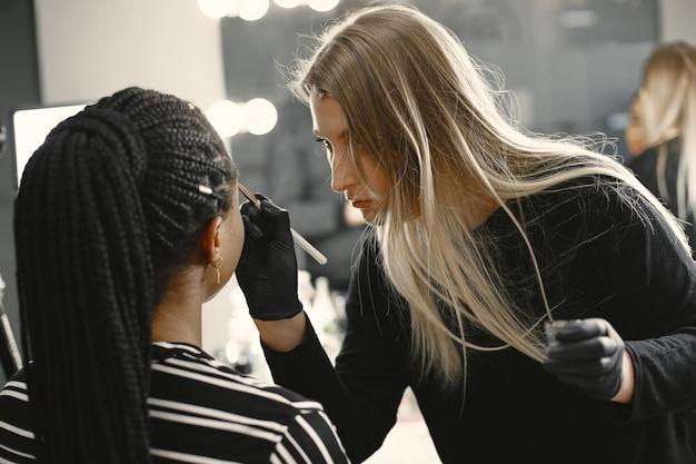 Chica africa. mujer haciendo cejas. chicas en un salón de belleza.