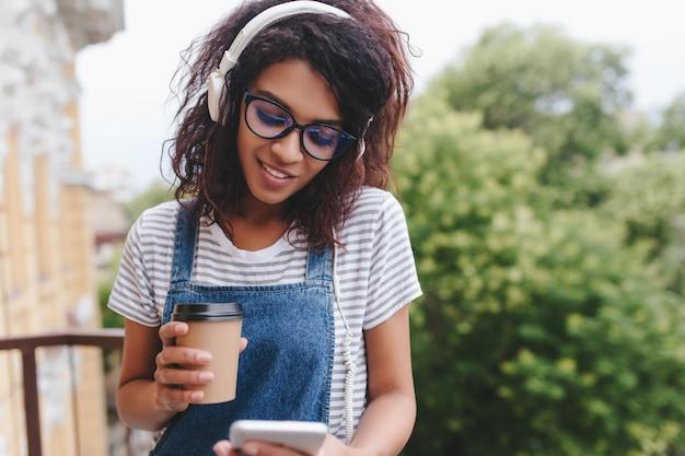 Chica africana de moda con mensajes de texto de pestañas largas y sosteniendo una taza de café en la naturaleza