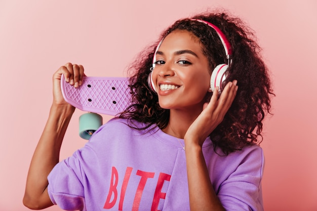 Chica africana soñadora escuchando música en auriculares grandes. riendo atractivo modelo femenino negro posando con longboard en pastel.