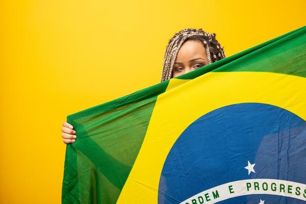 Chica afro animando al equipo brasileño favorito, sosteniendo la bandera nacional en amarillo.