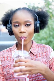Chica afro negra en traje étnico con auriculares sentado en un café al aire libre, escuchando música y bebiendo cócteles de leche