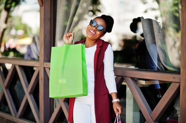Chica afroamericana casual con bolsas de colores caminando al aire libre. elegante mujer negra de compras.