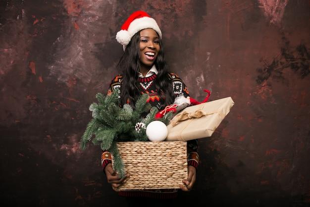 Chica afroamericana con decoraciones de navidad en una caja