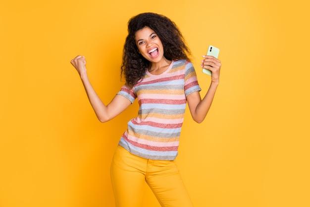 Chica afroamericana extática que usa el teléfono celular levanta los puños para celebrar el premio de la lotería en línea