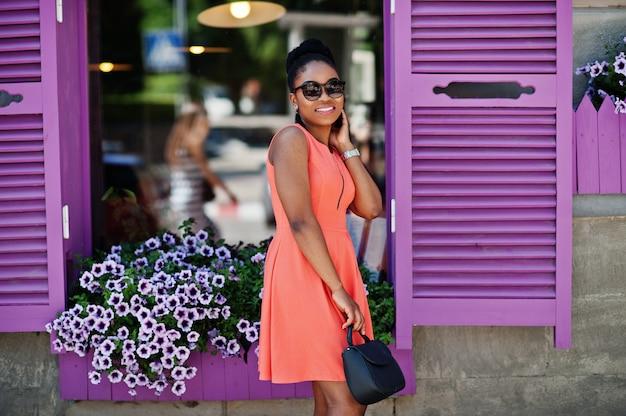 Chica afroamericana en gafas de sol, vestido de durazno y bolso posado contra ventanas moradas.