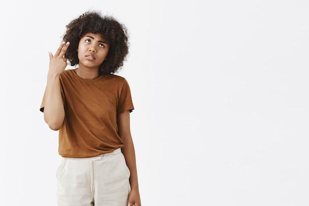 Chica afroamericana insatisfecha melancólica con peinado rizado en camiseta marrón muriendo de aburrimiento y molestia con los párpados rodantes haciendo disparos de pistola en la cabeza