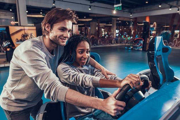Chica afroamericana montando coche arcade de videojuegos. el tipo blanco está ayudando.