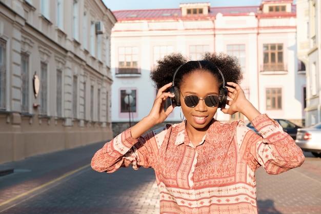 Chica afroamericana negra tiene un paseo por la ciudad de noche y escucha música en auriculares. chica con gafas de sol en verano sonríe y mirando el atardecer.